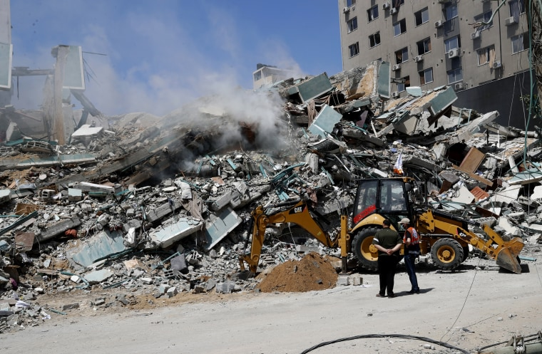 Workers clear rubble from a building that was destroyed by an Israeli airstrike on Saturday that housed The Associated Press, broadcaster Al-Jazeera and other media outlets, in Gaza City on May 16, 2021.