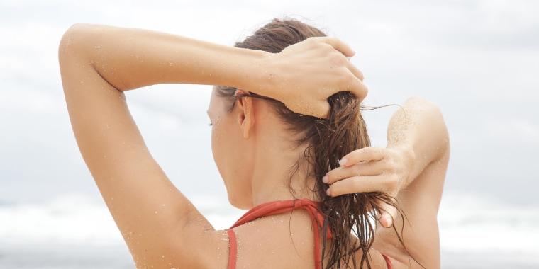 Brunette Woman applying scalp sunscreen on the beach