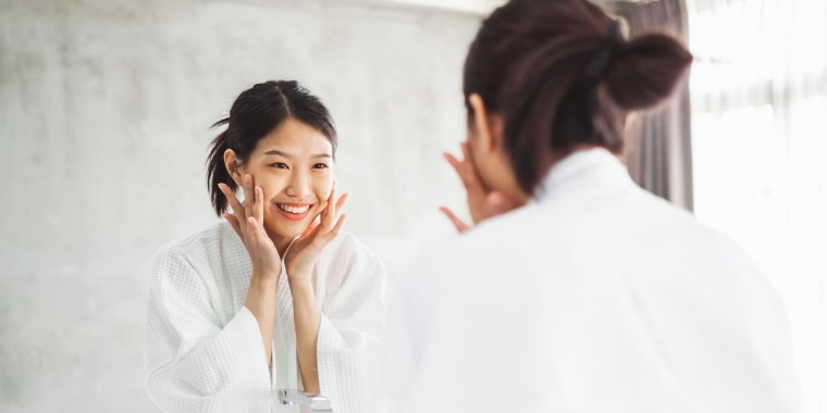 Woman Looking At Her Face On Mirror In Bathroom