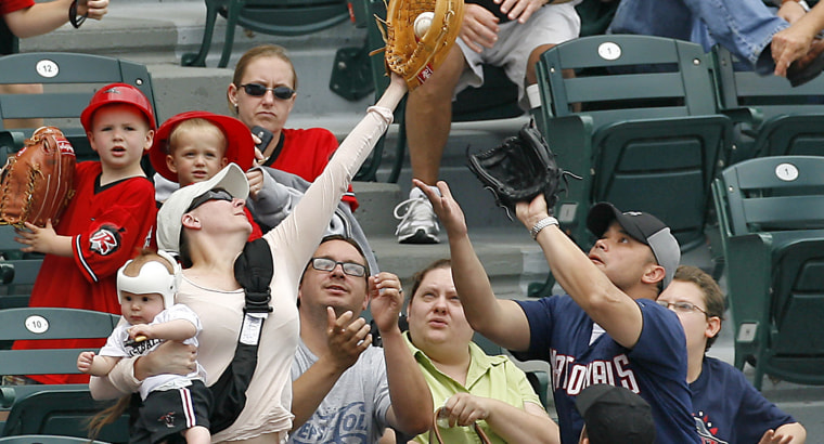 In this photo made May 15, 2011, Tiffany Goodwin, of  Fredericksburg Va., robs her husband Allen, at right with glove, of a foul ball while holding 8-month-old son Jerry, during a minor league baseball game between the Richmond Flying Squirrels and Harrisburg Senators at The Diamond in Richmond Va.