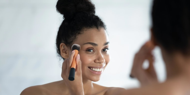 Woman looking in the mirror putting on makeup with a brush