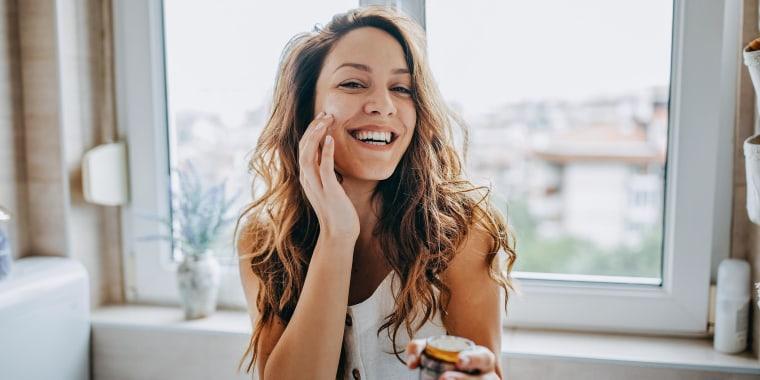 Woman applies facial cream in her bathroom