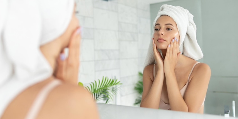 Woman using skin face cream lotion, while looking in the mirror in her bathroom