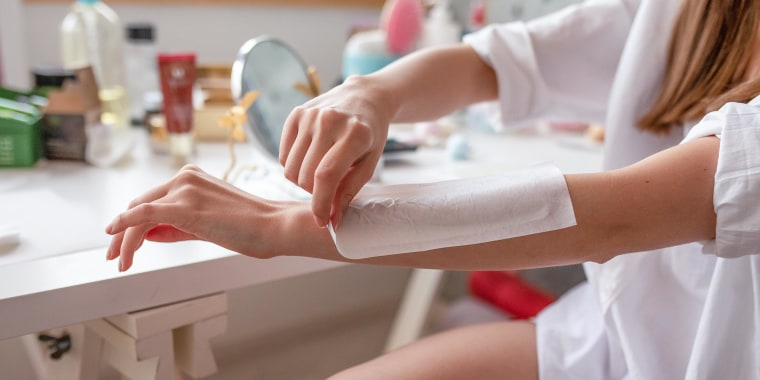 Woman waxing her arm with a wax strip at home