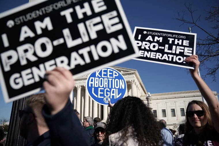 Anti-abortion activists try to block the sign of an abortion rights activist during the 2018 March for Life in Washington on January 19, 2018.