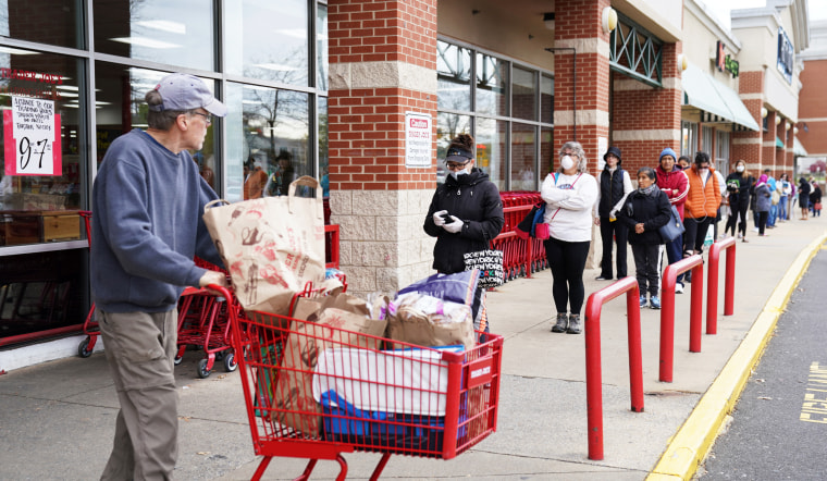 A shopper passes near a self-distancing queue outside Trader Joe's in Bailey's Crossroads, Va., on March 31, 2020.
