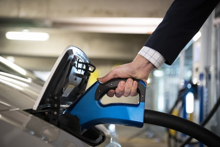 A man charges an electric vehicle at an EVgo charging station at Union Station in Washington on April 22, 2021.