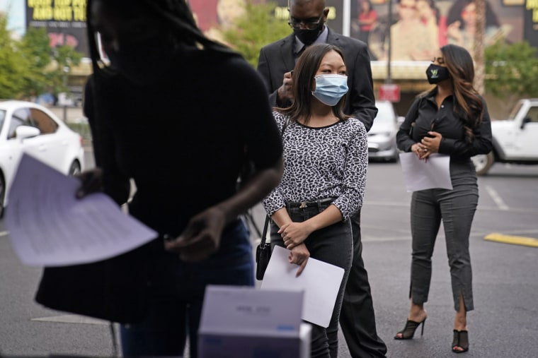 Image: People wait in line, resumes in hand, while waiting to apply for jobs during an outdoor hiring event for the Circa resort and casino, on April 27, 2021, in Las Vegas.
