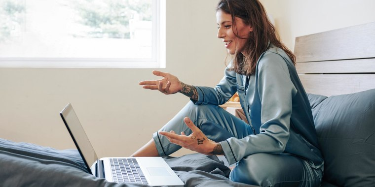 Woman in silk pajamas sitting on bed and having video conference. See the best silk pajamas for women to try in 2021. Shop silk pajamas that are affordable and washable from Lunya, Nordstrom and more.