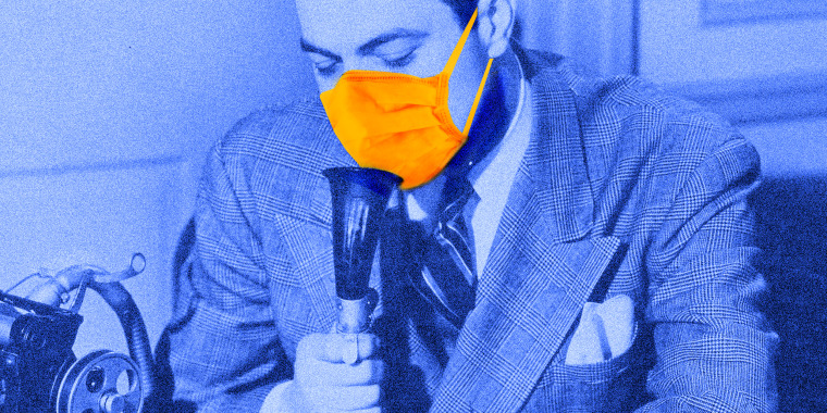 Photo illustration: A person wearing a suit and a protective mask speaking into a dictaphone.