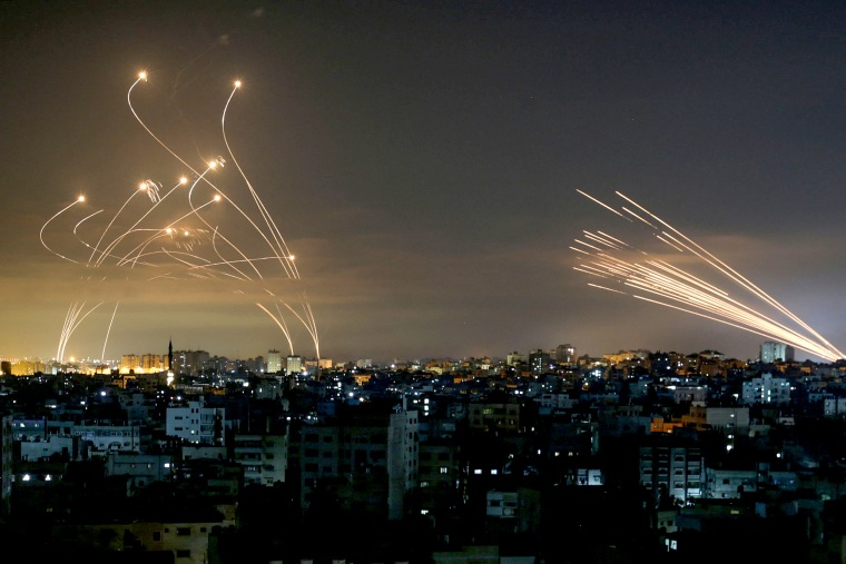 Image: The Israeli Iron Dome missile defense system, left, intercepts rockets, right, fired by the Hamas movement towards southern Israel from Beit Lahia in the northern Gaza Strip as seen in the sky above the Gaza Strip overnight on May 14, 2021.