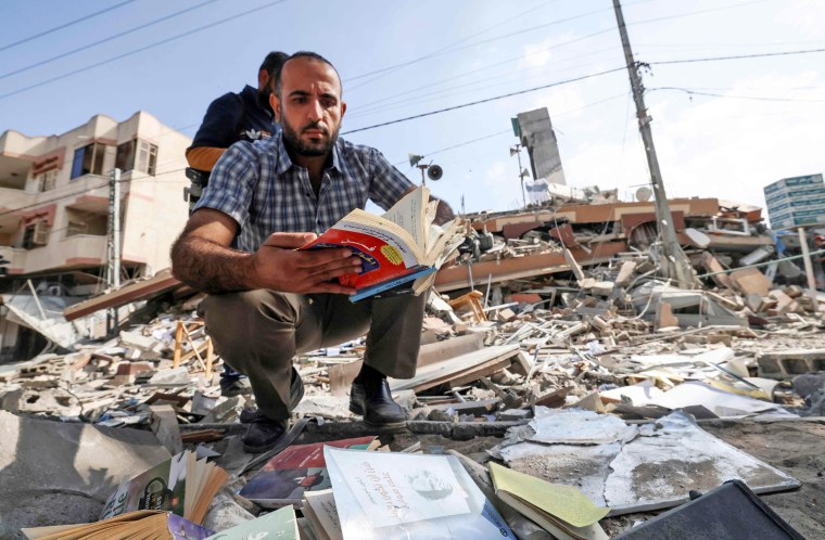 A Palestinian man holds a book he removed from under the rubble of the Kuhail building which housed Samir Mansour's bookstore in Gaza City.