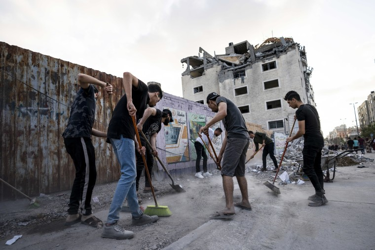 People clean the streets on Friday, beside a building that was damaged in an air-strike.