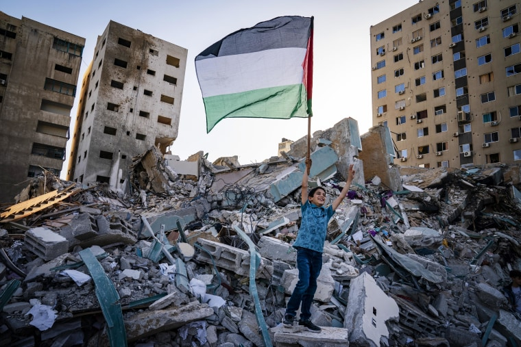 A child raises a Palestinian flag following a cease-fire reached between Israel and Hamas, in Gaza City, on Friday.