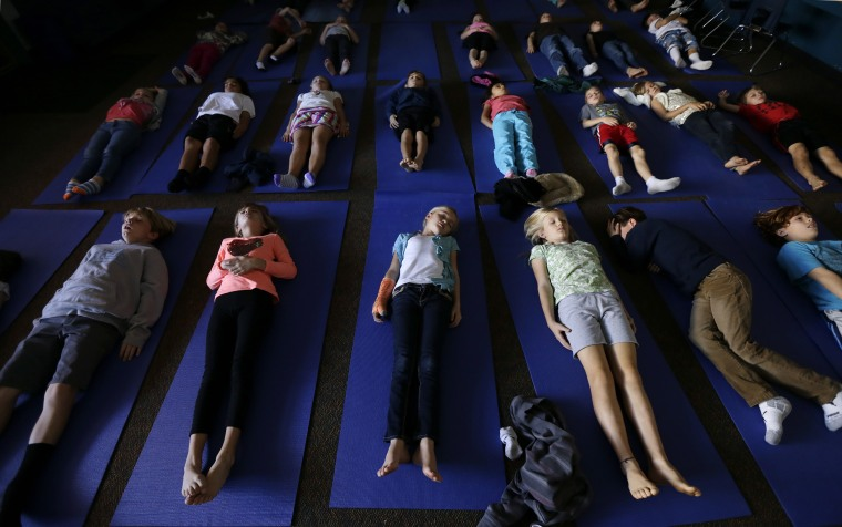 Image: A class of third graders wind down with the lights out at the end of a yoga class at an elementary school in Encinitas, Calif.