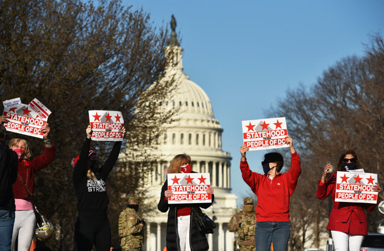 Activists hold signs as they take part in a rally in support of DC statehood near the Capitol on March 22, 2021.