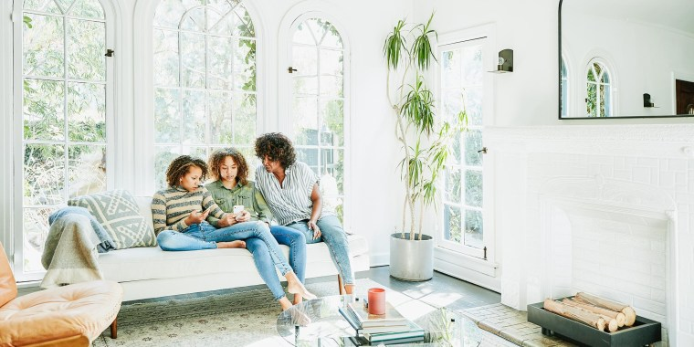 Mother and daughters sitting in living room watching video on smart phone