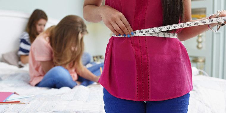 Teenage girl measuring her waist