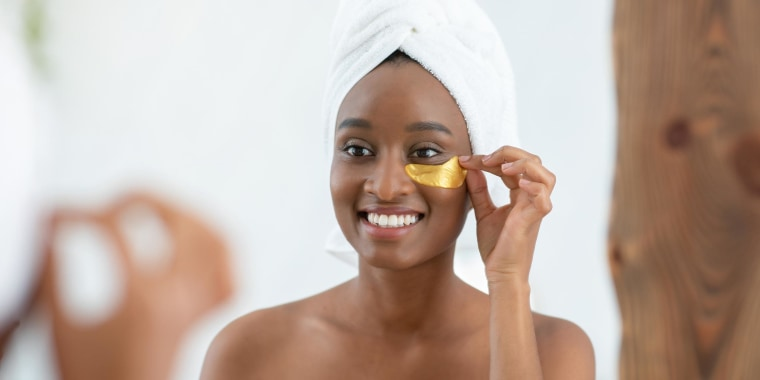 Woman wearing a white towel on her head, putting on gold patches under her eyes, while looking in the mirror