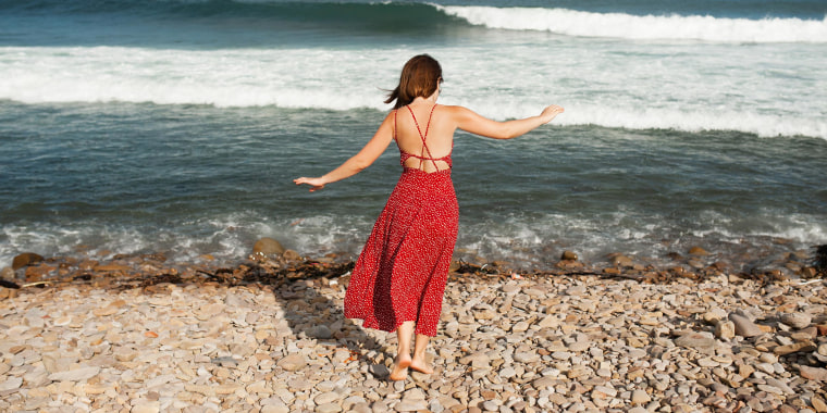 Woman In Red Long Dress With Walks On Rocky Beach Near The Ocean In Summer On Sunny Day