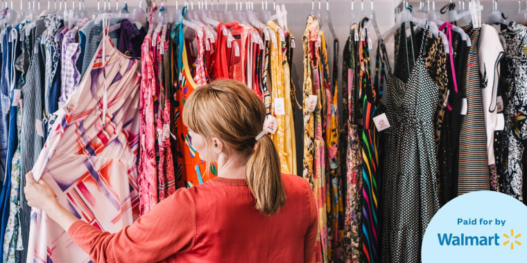 Woman looking at dress hanging on rack while standing at store