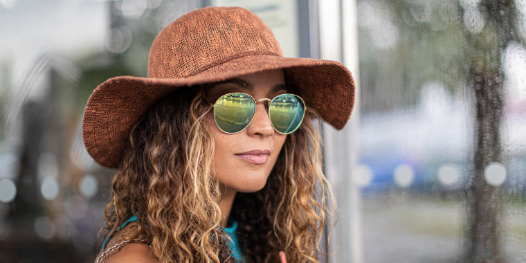Woman wearing hat and sunglasses while standing outdoors in city