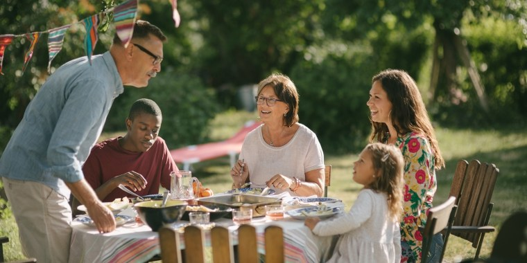 Senior man and granddaughter talking while having lunch with family in backyard during party