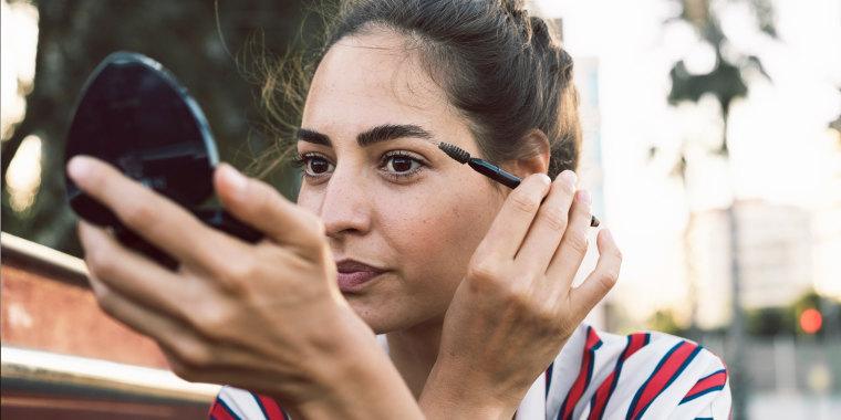 Portrait of woman applying mascara