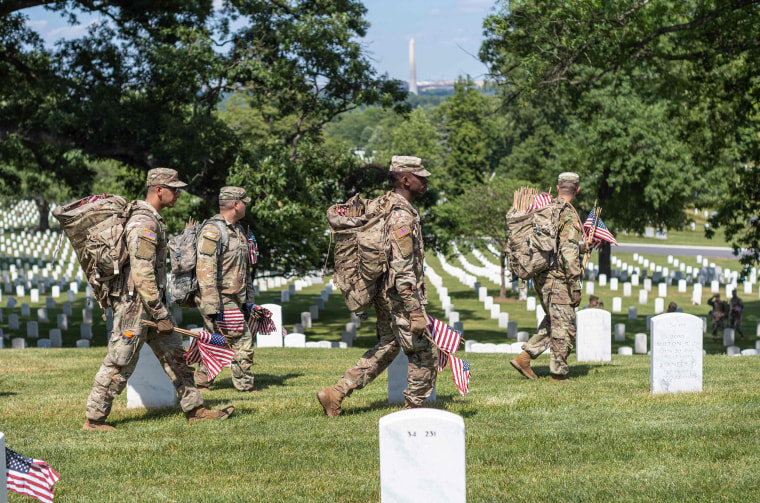"""Air Force members place miniature US flags at graves in Arlington National Cemetery in Arlington, on May 27, 2021. - The \""""Flags In\"""" tradition takes place ahead of Memorial Day which honors service members who died while serving in the military."""