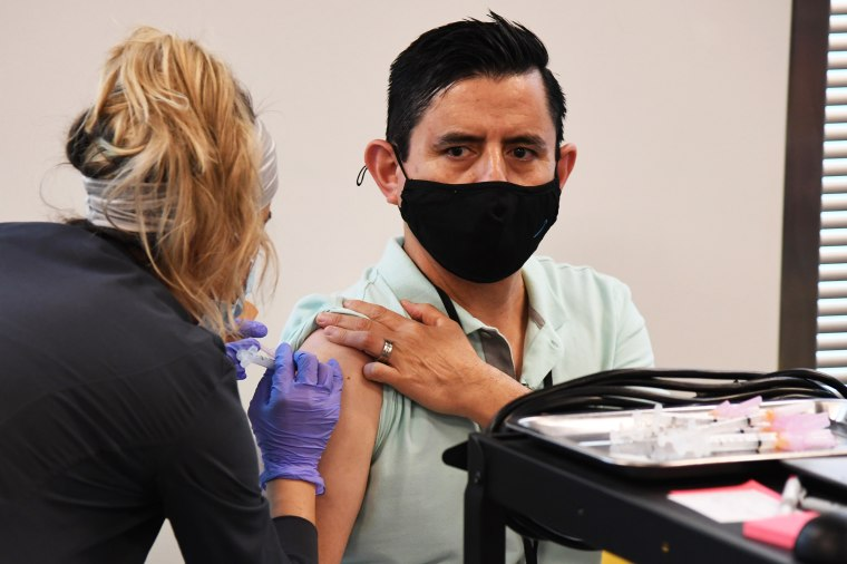 Concentra registered nurse Deysi Fleix administers a Moderna COVID-19 vaccination to Amazon employee Juan Nunez at a fulfillment center on March 31, 2021 in North Las Vegas, Nev.