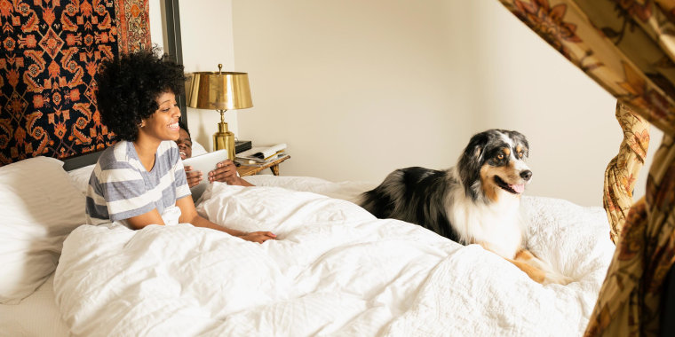 Woman and partner sitting with dog in bed