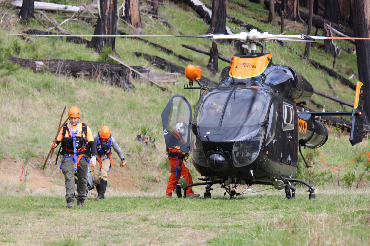 Image: Jackson County Searchers exit a Brim Aviation helicopter after finding Harry Burleigh