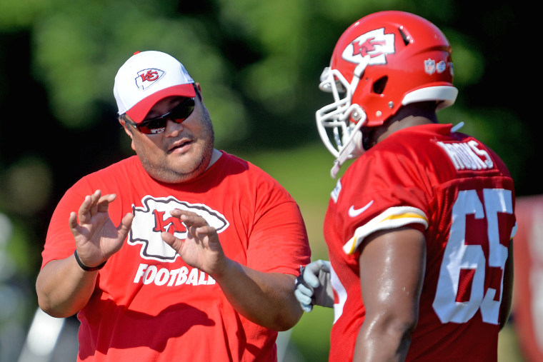 Kansas City Chiefs assistant offensive line coach Eugene Chung talks with lineman Tavon Rooks during NFL football training camp practice on Aug. 2, 2015, in St. Joseph, Mo.