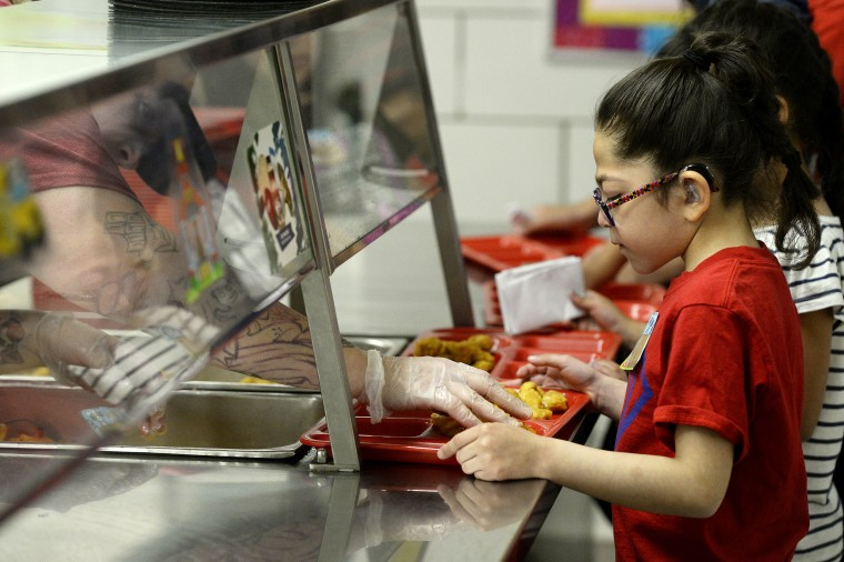 Image: A student gets a handful of fries on her tray during North Star Elementary School's free summer lunch program on June 5, 2017, in Thornton, Colo.