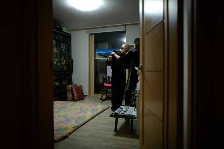 Image: Kim Se-Rin takes off his jacket with help from his daughter Kim Young-Soon in his bedroom at his home in Seoul.