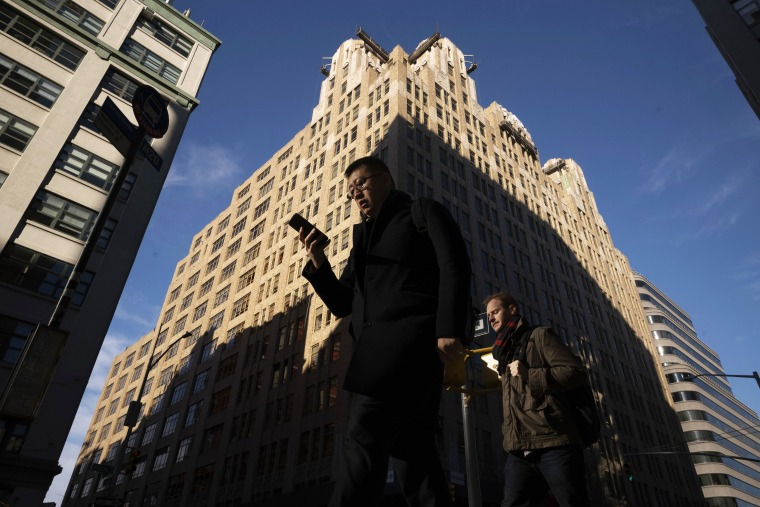 A man walks beneath a building in New York City checking his cellphone Dec 17. 2018.