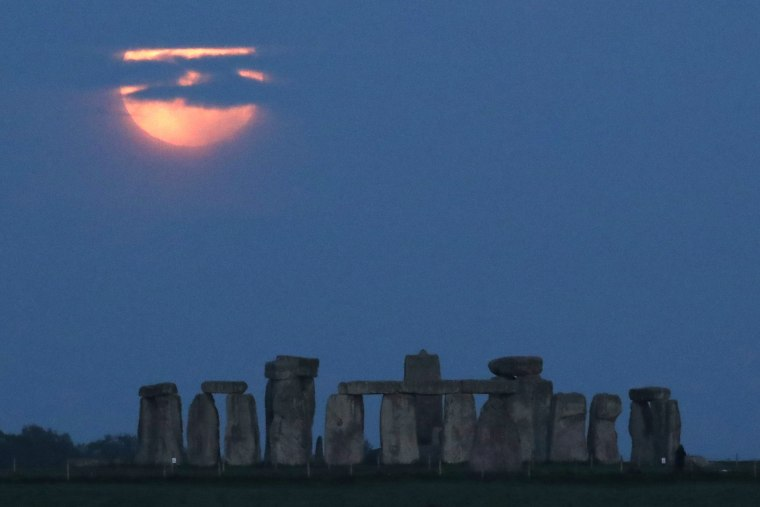 The Super Flower Blood Moon looms over Stonehenge near Amesbury, Britain, on May 26, 2021.
