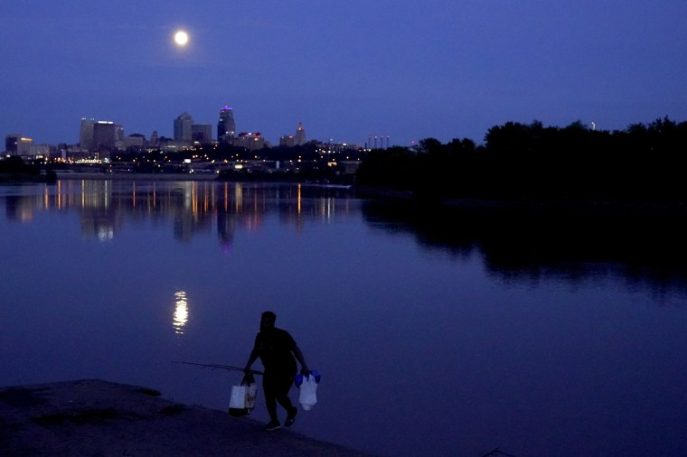 A man leaves after fishing in the Missouri River as the nearly full Super Flower Blood Moon rises over Kansas City, Mo., May 25, 2021.