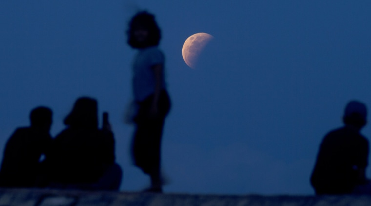 Residents watch the lunar eclipse at Sanur beach in Bali, Indonesia, on May 26, 2021.