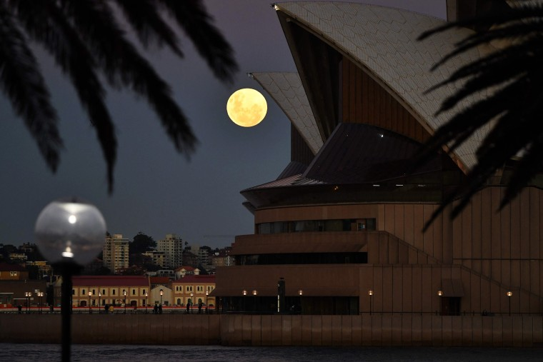 The Super Flower Blood Moon rises over the Sydney Opera House in Sydney on May 26, 2021.