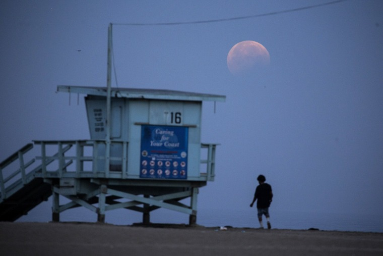 A woman watches as the Super Flower Blood Moon sets over Santa Monica, Calif., on May 26, 2021.