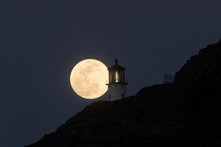 A Super Flower Blood Moon rises over the Makapuu lighthouse in east Oahu, Honolulu, Hawaii, on May 25, 2021.