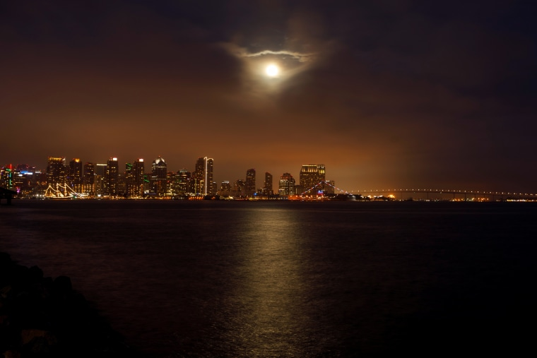 A Super Flower Blood Moon rises through low clouds above the city of San Diego, Calif., on May 25, 2021.