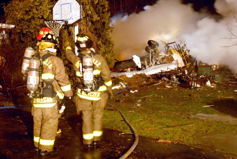 Firefighters look over the wreckage of Continental flight 3407 which lies amid smoke at the scene after crashing into a suburban Buffalo home and erupting into flames late on Feb. 12, 2009, killing all 48 people aboard and at least one person on the groun