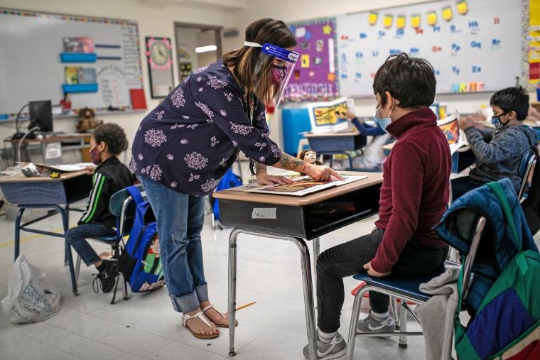 Teacher Elizabeth DeSantis helps a first grader during reading class at Stark Elementary School on Sept. 16, 2020 in Stamford, Conn.