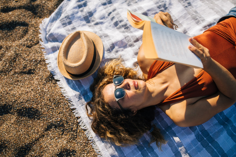 Woman lies on the beach reading a book