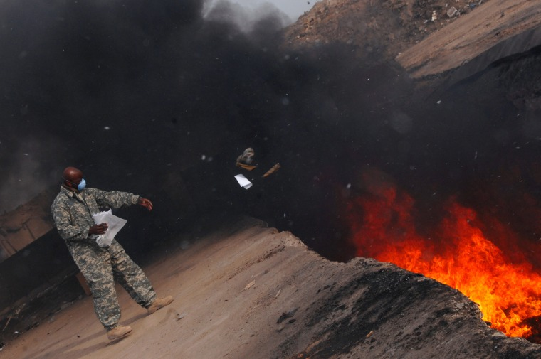 Image: A soldier tosses unserviceable uniforms into a burn pit in Iraq on March 10, 2008.