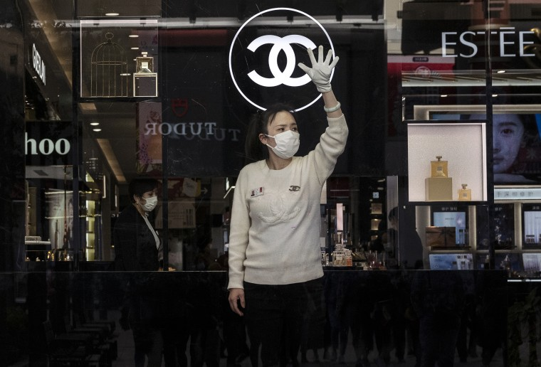 Image: A department store worker waves to potential customers at a department store for luxury brands on April 16, 2021 in Beijing.