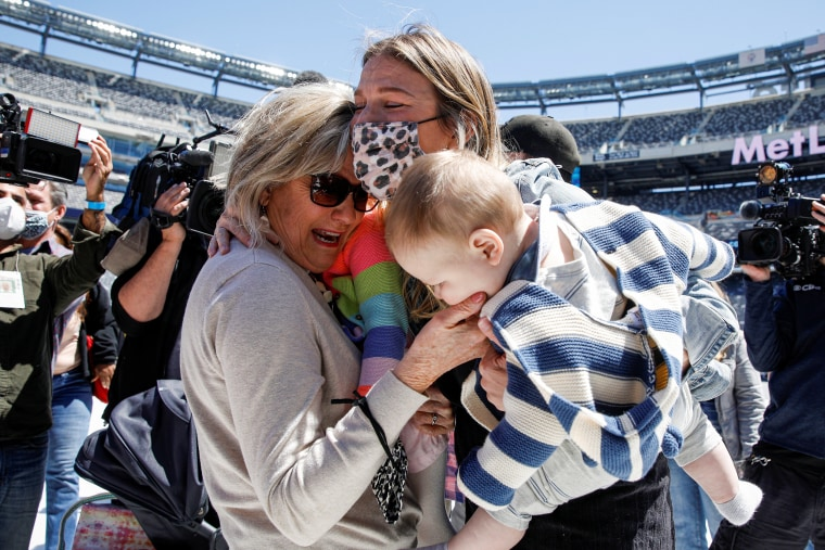 Image: Peggy Broda meets her grandchild in person for the first time  during a mass reunion event at MetLife Stadium in East Rutherford, New Jersey