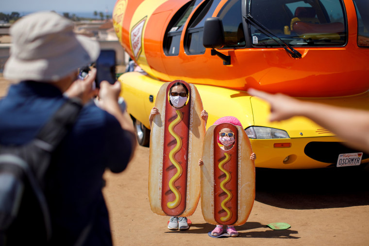 """Image: A family takes a picture at the Oscar Myer Wienermobile during a visit to \""""The Flower Fields \"""" in Carlsbad"""